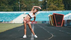 Sport, exercises outdoors. Girl doing stretching on stadium. Bending aside. Full body, looking aside stock footage
