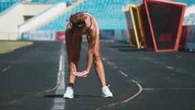 Sport, exercises outdoors. Girl doing stretching on stadium. Bending aside. Full body, looking aside stock video