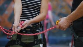 Sport extr?me Une femme attache les cordes de protection pour s'élever sous les instructions de l'entraîneur banque de vidéos