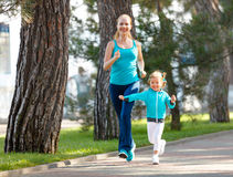 Sport family. Mother and baby daughter jogging run on nature. In summer stock photos