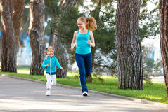 Sport family. Mother and baby daughter jogging run on nature royalty free stock image
