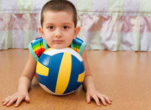 Sport fan. A little smiling boy is lying on the floor holding his head on the ball Royalty Free Stock Photos