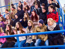 Sport fans clapping and singing on tribunes. Handrails in foreground. Royalty Free Stock Images