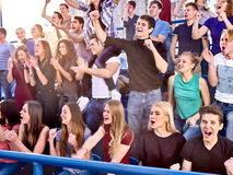 Sport fans hands up and singing on tribunes. Royalty Free Stock Photo