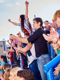 Sport fans hands up and singing  on tribunes Royalty Free Stock Images