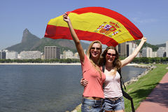 Sport fans holding a Spanish flag in Rio de Janeiro.mer in the background. Couple of female sport fans holding a Spanish flag in Rio de Janeiro with Christ the Royalty Free Stock Photos