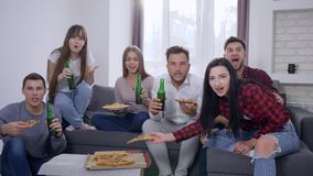 Sport fans watching decisive moment of game and happy for victory sitting on the sofa in front of TV eating pizza and stock video footage