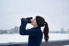 Sport female drinks water on jogging outside at cloudy winter day Royalty Free Stock Images
