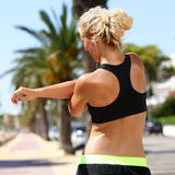 Sport female runner stretching arms before running. Woman in fitness sports bra view from the back doing stretching exercises for the shoulder muscles before a Stock Photos