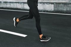 sport Fermez-vous des jambes masculines fonctionnant sur la route dehors Images stock