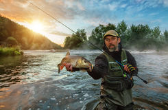 Sport fisherman holding trophy fish. Outdoor fishing in river. During sunrise. Hunting and hobby sport