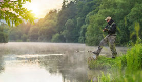 Sport fisherman hunting fish. Outdoor fishing in river. Sport fisherman hunting predator fish. Outdoor fishing in river during sunrise. Hunting and hobby sport Royalty Free Stock Images
