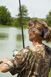 Sport fishing. Female contestant is using quality rod and reel for fishing on the lake Stock Image