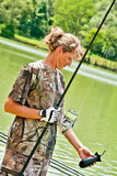 Sport fishing. In order to lure more fish female contestant is checking plastic rocket used as a boilie carrier before making a throw bait far away from the Royalty Free Stock Photography