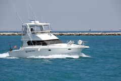 Sport Fishing Boat. A white sport fishing boat, flying the US Yacht Ensign, heads towards the open sea stock photos