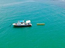 Aeria view of sport fishing boat with banana boat ride attach on the back. Sport fishing boat with banana boat ride attach on the back. In Praia do Forte beach stock images