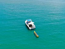 Aeria view of sport fishing boat with banana boat ride attach on the back. Sport fishing boat with banana boat ride attach on the back. In Praia do Forte beach stock image