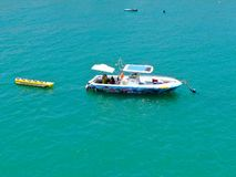 Aeria view of sport fishing boat with banana boat ride attach on the back. Sport fishing boat with banana boat ride attach on the back. In Praia do Forte beach stock photo
