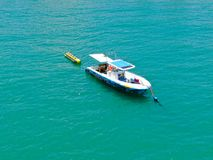 Aeria view of sport fishing boat with banana boat ride attach on the back. Sport fishing boat with banana boat ride attach on the back. In Praia do Forte beach royalty free stock photos