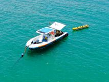 Aeria view of sport fishing boat with banana boat ride attach on the back. Sport fishing boat with banana boat ride attach on the back. In Praia do Forte beach stock photos