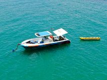 Aeria view of sport fishing boat with banana boat ride attach on the back. Sport fishing boat with banana boat ride attach on the back. In Praia do Forte beach royalty free stock image