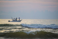Sport fishing just off the Florida coast at sunrise. Guys saltwater fishing in the morning stock photography