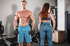 Sport fit couple at gym. work in pairs with dumbbells Royalty Free Stock Images