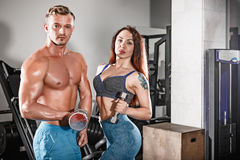 Sport fit couple at gym. work in pairs with dumbbells Royalty Free Stock Photo