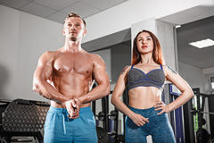 Sport fit couple at gym. work in pairs with dumbbells Stock Image