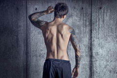 Sport fit muscular tattooed guy from back in loft space. Concrete walls behind royalty free stock photography