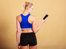 Sportswoman using mobile phone in the gym. Sport, fitness, active lifestyle. Sportswoman using mobile phone in the gym Stock Images