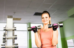 Sport, fitness, bodybuilding, teamwork and people concept - young woman flexing muscles on gym machine Stock Photos