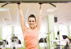 Sport, fitness, bodybuilding, teamwork and people concept - young woman flexing muscles on gym machine Royalty Free Stock Photo