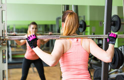 Sport, fitness, bodybuilding, teamwork and people concept - young woman flexing muscles on gym machine royalty free stock images