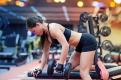 Young woman flexing muscles with dumbbell in gym Royalty Free Stock Photography
