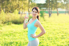 Sport and fitness concept - beautiful smiling woman drinking water from bottle Stock Photo