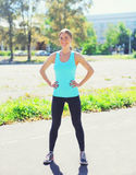 Sport and fitness concept - beautiful smiling young woman preparing to run in city Royalty Free Stock Photo