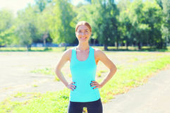 Sport, fitness concept - beautiful smiling young woman preparing to run in park Royalty Free Stock Images