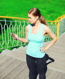 Sport and fitness concept - beautiful young woman listens to music and using smartphone in city. Park Stock Photography
