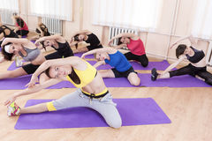 Sport and Fitness Concept. Group of Seven Female Athletes Performing Stretching Exercising Stock Photos