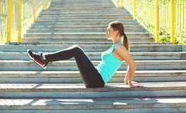 Sport and fitness concept - young woman doing stretching exercises Stock Photo