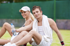 Sport and Fitness Concepts: Happy Caucasian Couple In Tennis Gea. R Posing On Court During Waterbrake. Horizontal Image Composition Royalty Free Stock Photography
