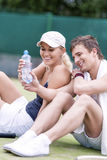 Sport and Fitness Concepts: Happy Caucasian Couple In Tennis Gea. R Posing On Court During Waterbrake. Vertical Image Composition Royalty Free Stock Photos