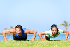 Sport fitness couple doing push ups. Outdoor. Young athletes doing pushups exercise outside on grass in summer. Caucasian men sports model and Asian women Stock Photo