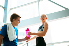 Sport fitness couple relaxing after training in light interior Royalty Free Stock Image