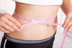 Sport, fitness and diet concept - closeup of trained belly with measuring tape Stock Photo
