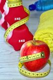 Sport, fitness, diet and objects concept - close up of dumbbell and red apple with measuring tape. Fitness equipment. Dumbbell towel mineral water apple and Stock Photos