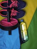 Sport and fitness equipment. On green mat, roll for crunches, shoes, bottle of water, cloth stock photos