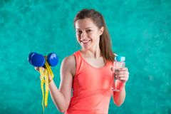 Sport fitness girl with dumbbells, bottle of water and tape measure for diet  -  on the turquoise  background.Sweets are u. Nhealthy. Junk Food. Dieting, Healthy Stock Photography