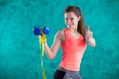 Sport fitness girl with dumbbells and tape measure for diet  - isolated on the turquoise  background. Sweets are unhealthy. Junk Food. Dieting, Healthy Eating Royalty Free Stock Image